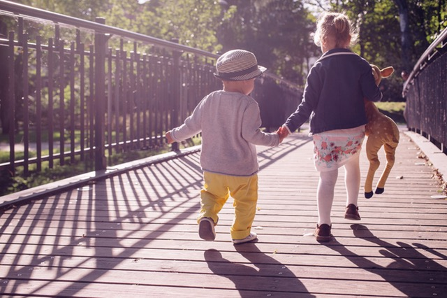 Image of small children hand-in-hand walking over bridge in the sunshine.