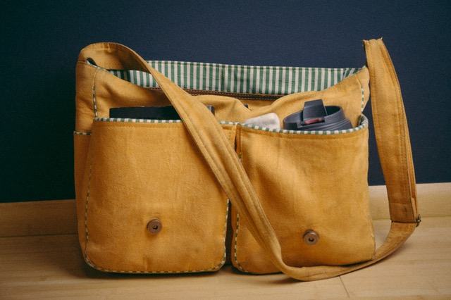 Camel suede bag with front pockets filled with notebooks, pens, coffee thermos