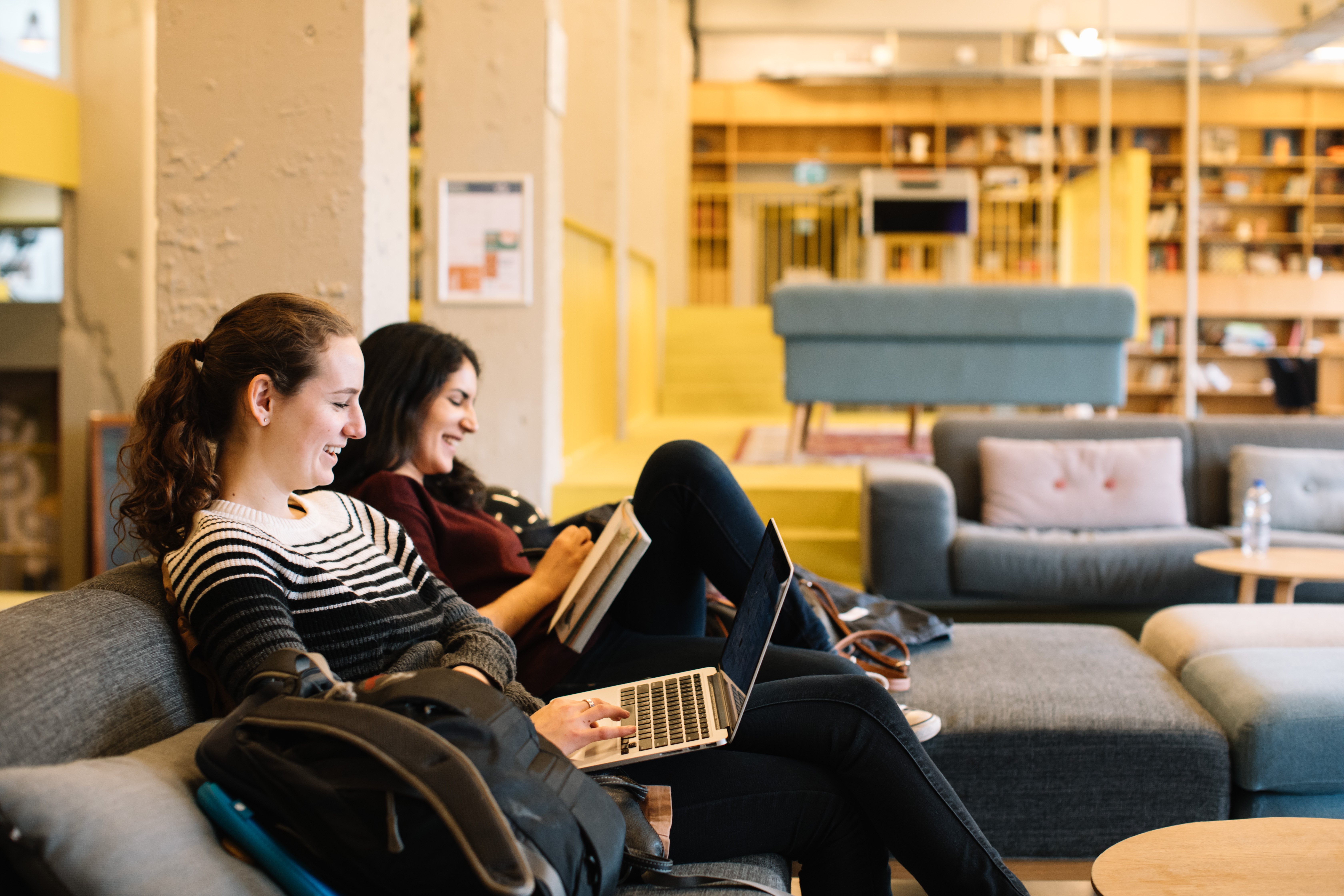 Two students working on their laptops in a campus lounge