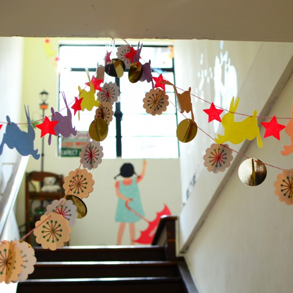 girl standing at the top of the stairs in an elementary school hallway with decorative banners in the foreground