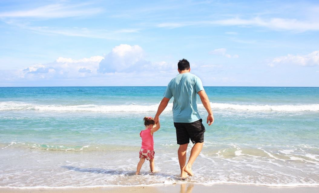 Father and daughter holding hands and walking on the beach.