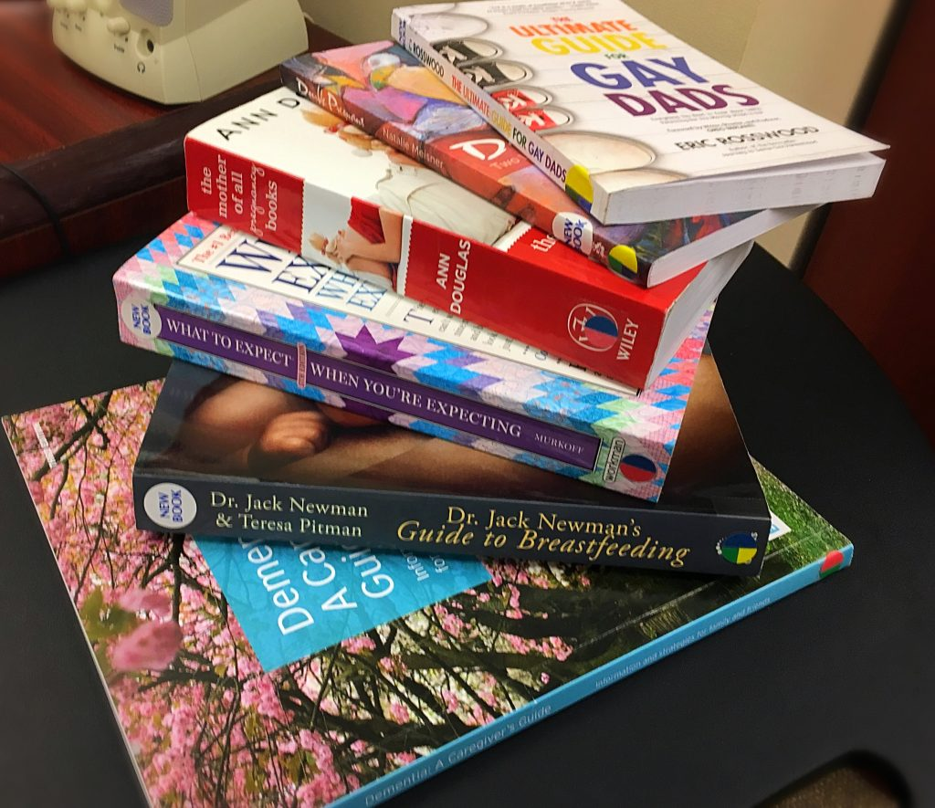 Image of cascading books from the Family Care Office Library on a table.