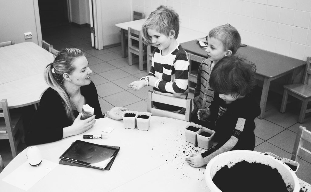 Teacher sitting with 3 young children at a table touching soil with their hands.