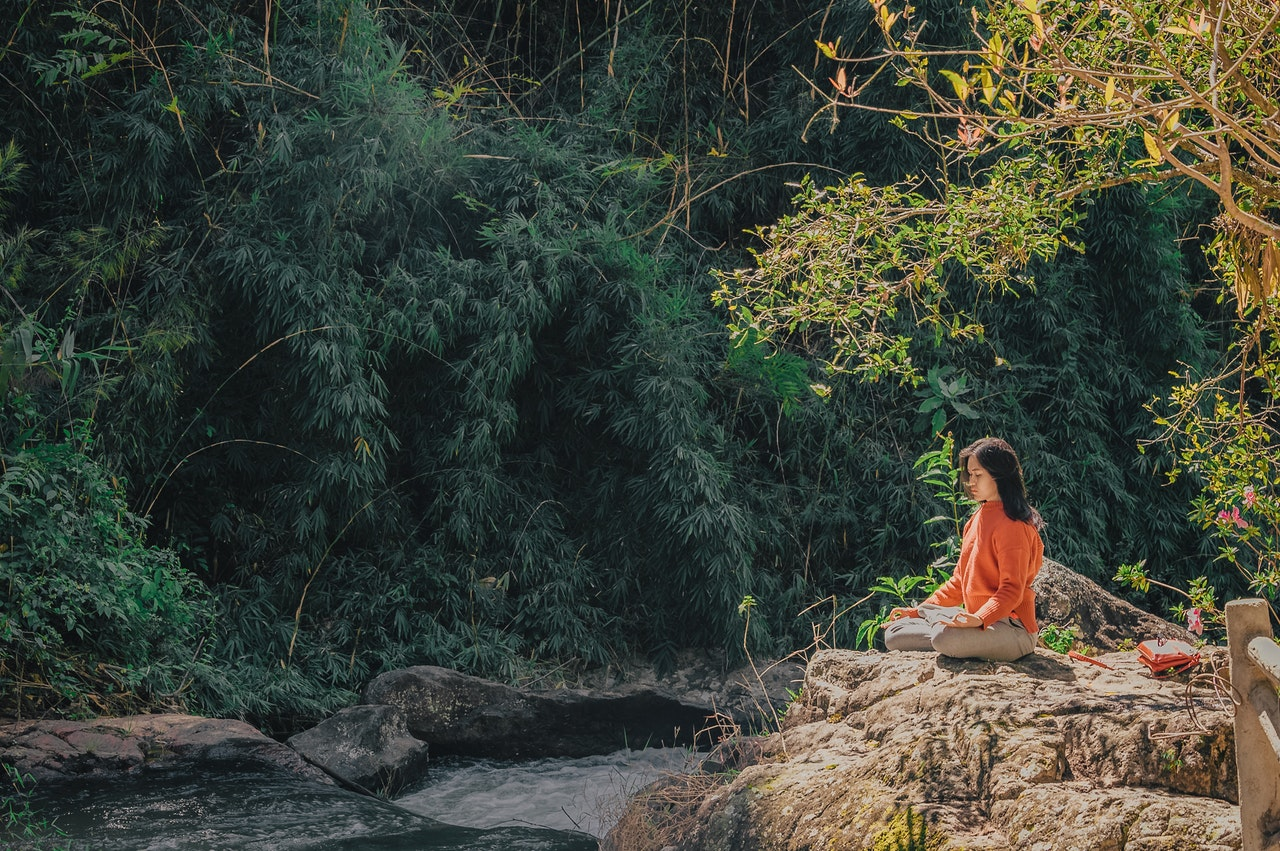 Woman meditating in forest.