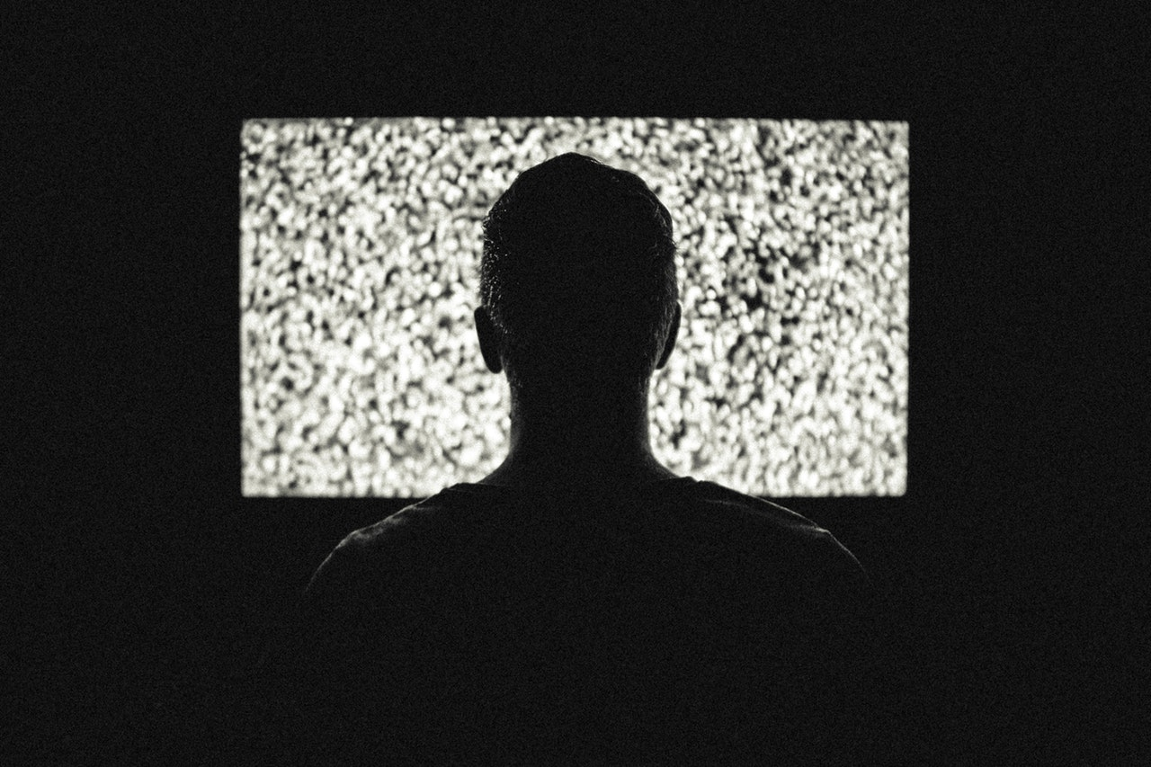 Man sitting infront of television in the dark.