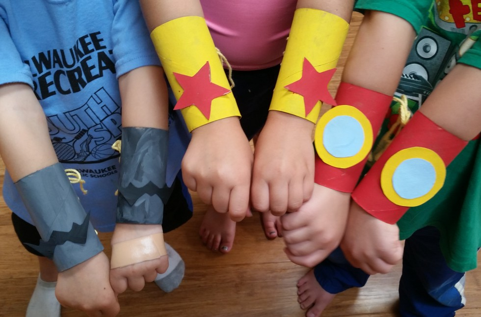 Children holding their arms up with brightly coloured superhero wristband/cuffs on.