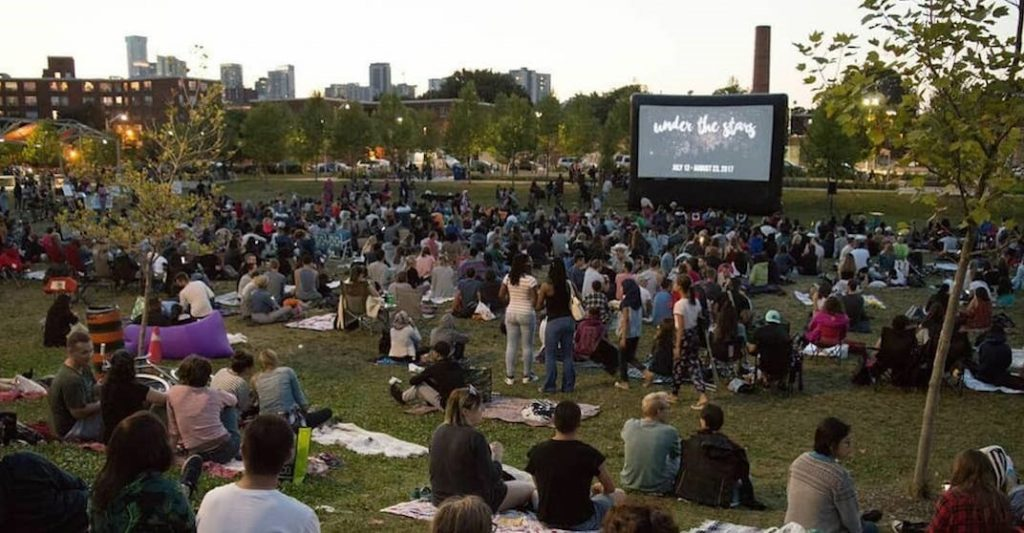 Many people sitting on blankets in a park watching a movie on a large screen.