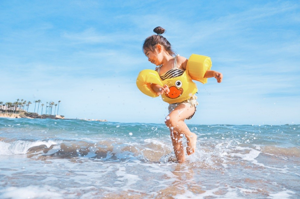 Little girl running in the ocean with a yellow flotation device.