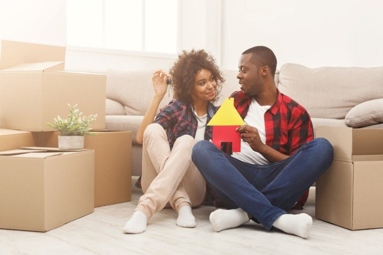 Two couples sitting on the floor with moving boxes looking at each other.