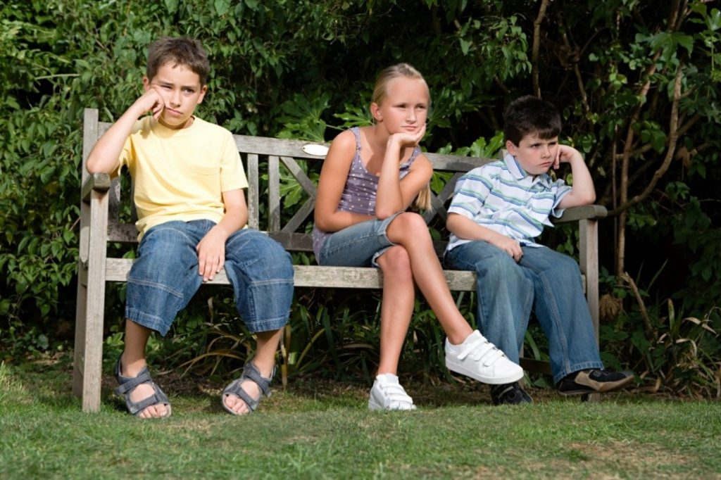 Three children sitting on a brown bench, looking bored.