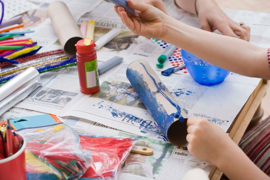 A table with newspaper and child painting a construction tube with paint.