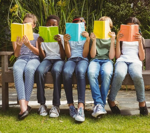 Five children sitting on a bench reading colourful books.