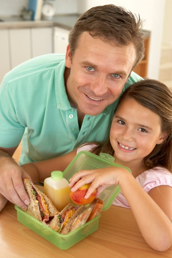 A dad and daughter packing a healthy lunch in a green reusable container.