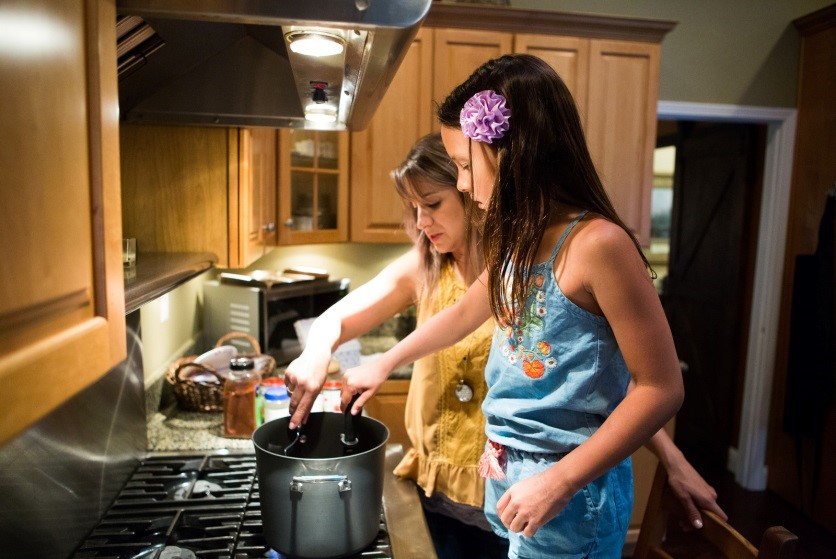 A mom and daughter cooking pasta together over the stove.
