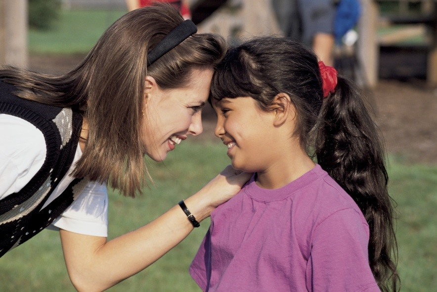 A woman in a white shirt smiling at a young child wearing a purple shirt.