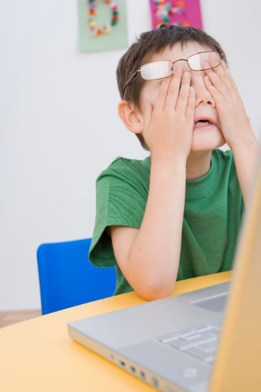 Child sitting at a desk working on a grey computer, with hands in his face feeling frustrated.