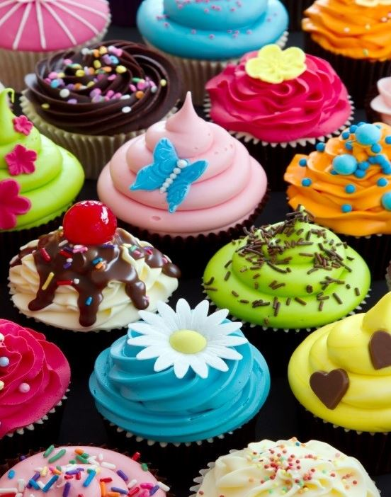 Chocolate cupcakes with brighly coloured icing.