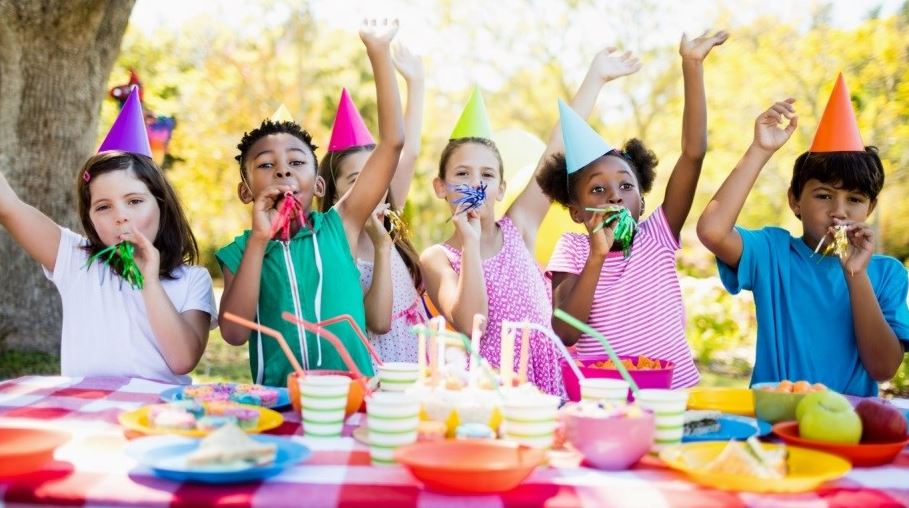 Six children sitting at a picnic table with brighly coloured birthday hats and blowing whistles.