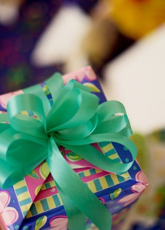 A blue birthday gift wrapepd with a green ribbon.