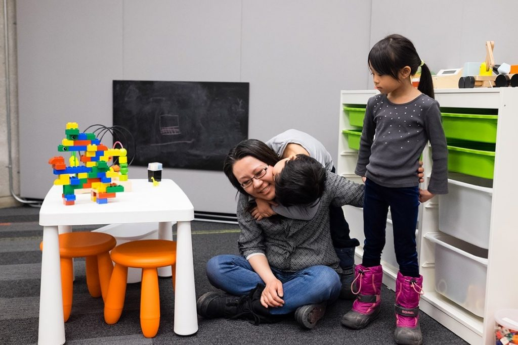 A student parent sitting on the floor, cross-legged with a child hugging them. Another child standing beside them, in the Robarts Family Study Space. A black chalkboard, child-sized furniture and toys are in the background.