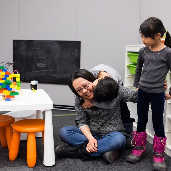 An student parent sitting on the floor, cross-legged with a child hugging them. Another child standing beside them, in the Robarts Family Study Space. A black chalkboard, child-sized furniture and toys are in the background.