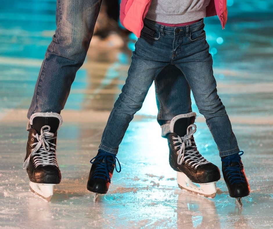 An adult skating on ice with a child of
