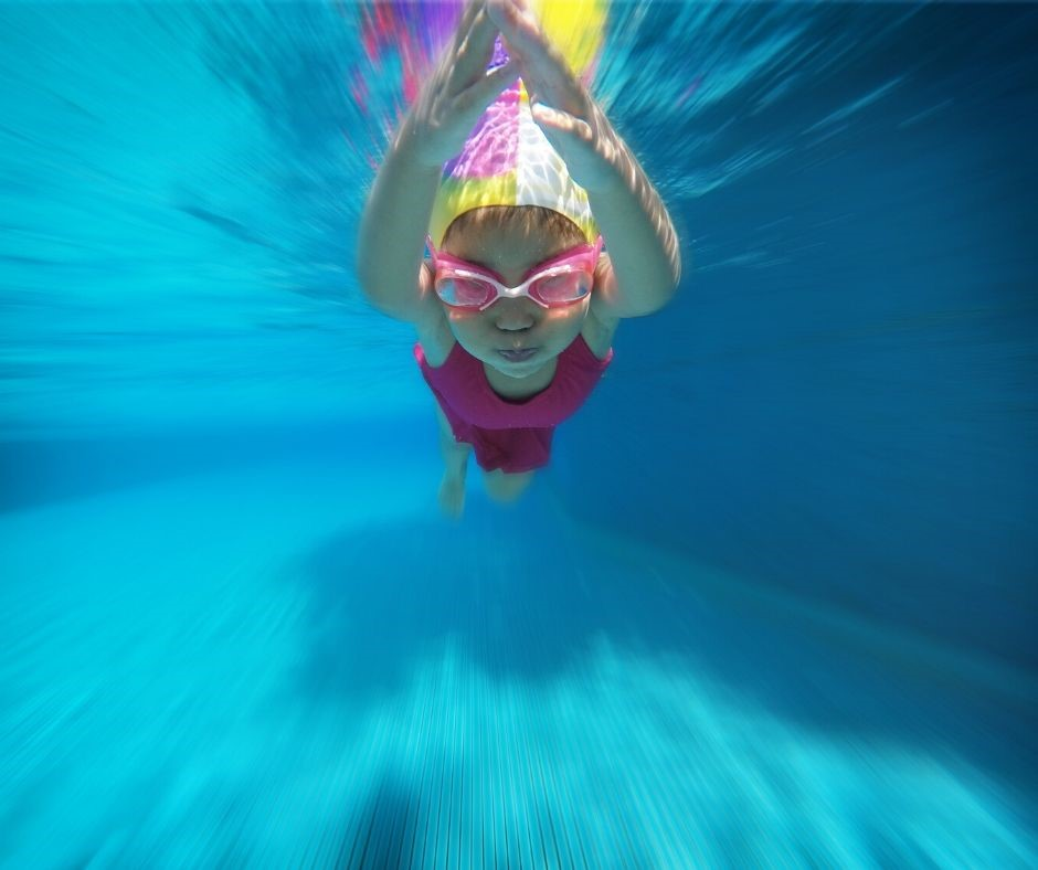 Child swimming in a pool wearing a pink swimsuit and goggles.