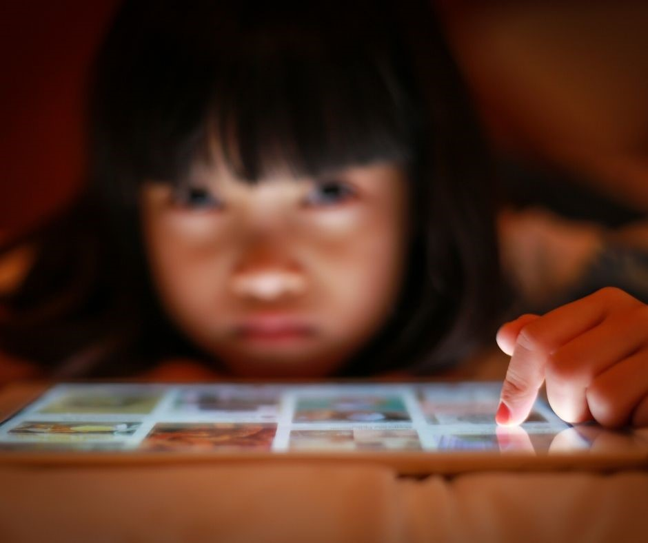 Small child touching an iPad screen.