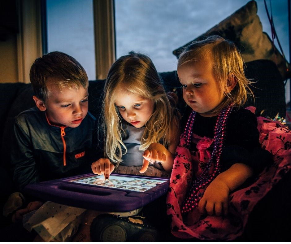 Kids sitting around and touching an ipad.