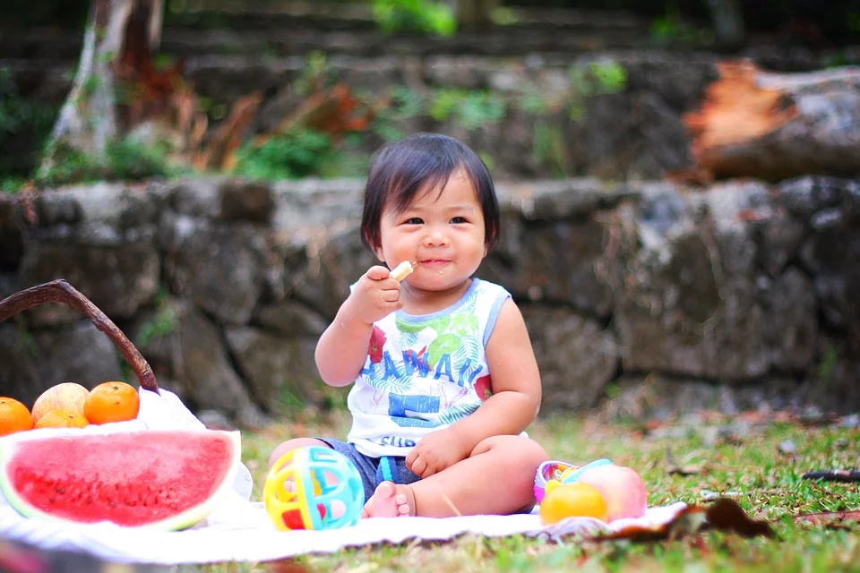 Baby sitting at a picnic eating fruits