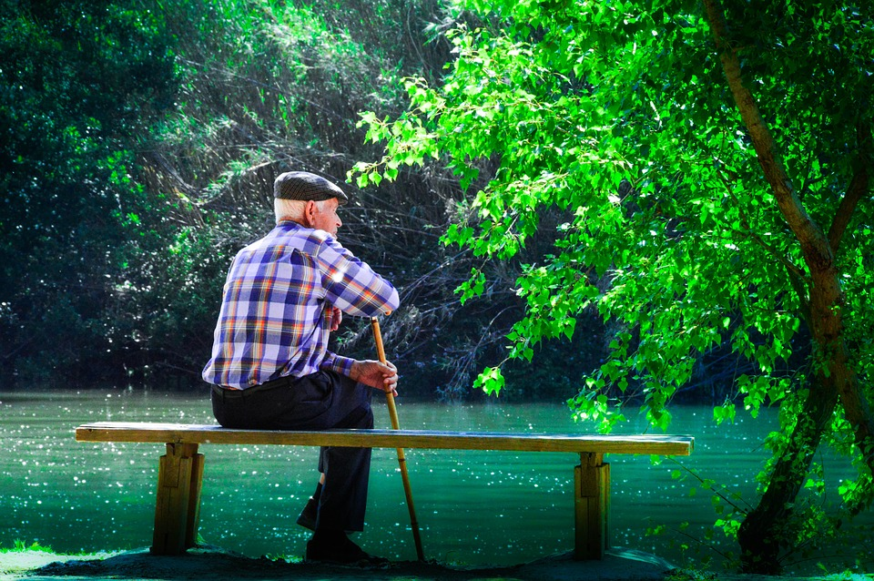Senior sitting on a bench by the lake, while holding a cane