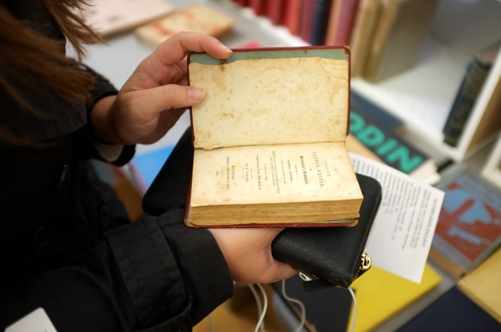 photo of a person holding an aged book from 1836