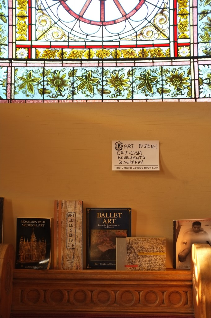 photo of art and dance books propped against the wall under stained glass
