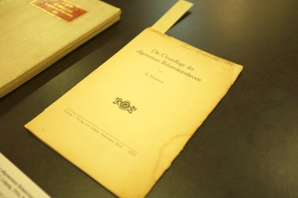 a title page (or perhaps a short pamphlet) By Albert Einstein lying on a table. The title is in German: Die Grundlage der allgemeinen Relativitäystheorie which is in english: Foundations of the General Theory of Relativity