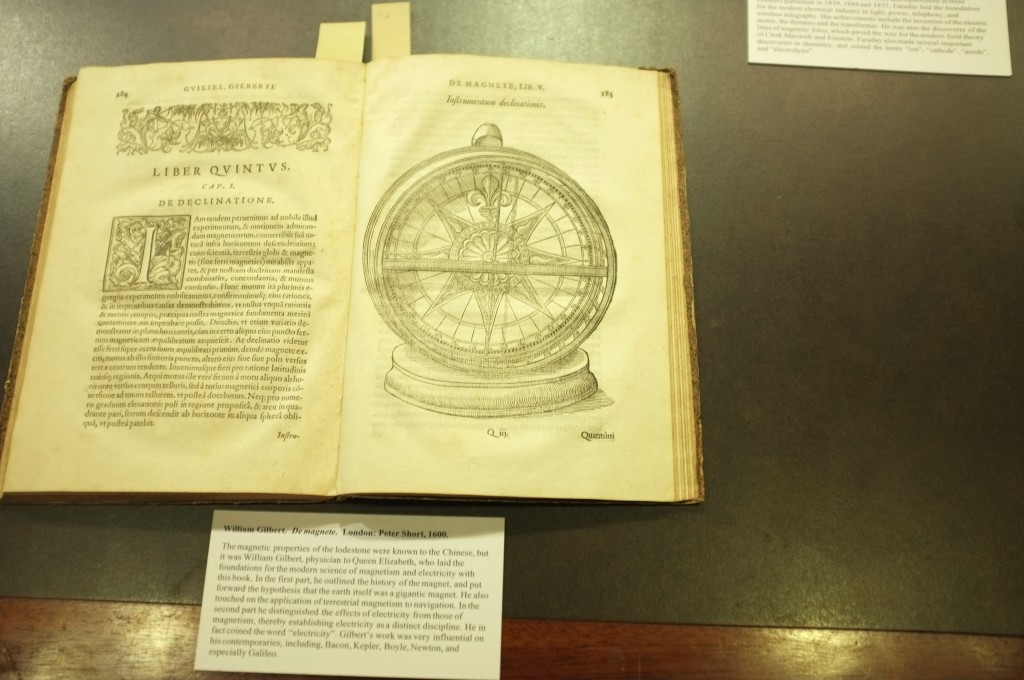 a picture showing a copy of De Magnete by William Gilbert open on a desk. The page shows a Compass showing declination.
