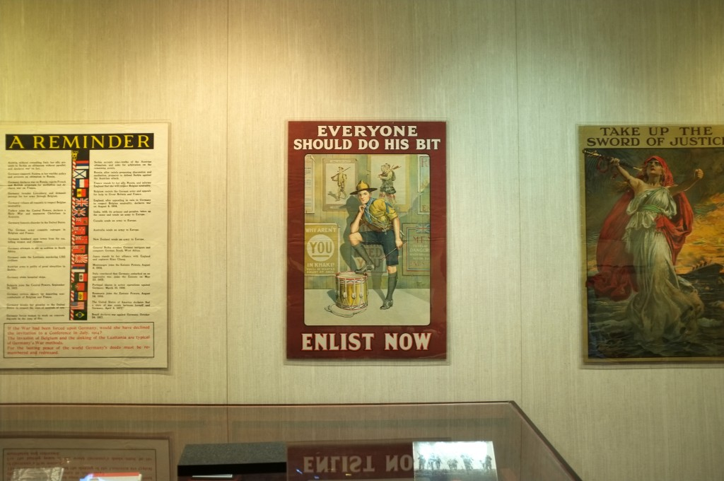 "Three propeganda posters from world war one on a wall. The first says ""A reminder"" and has some smaller text that can't be read from this distance. the second shows a youth in what looks like a scout uniform resting one foot on a drum and leaning over so his elbow is on that knee and his head is propped on his hands. Behind him in the poster are other posters encouraging people to enlist. The text of this poster states ""everyone should do his bit. Enlist now."" The third poster shows a women standing on a rock in the sea with a blue bliiowing toga-like dress and a red hooded cape. She is holding a sheathed sword in one hand and both arms are flung wide, she looks very passionate. In the background is a redish orange sky (like a sunset) and a ship in the sea. The text says ""take up the sword of justice"""