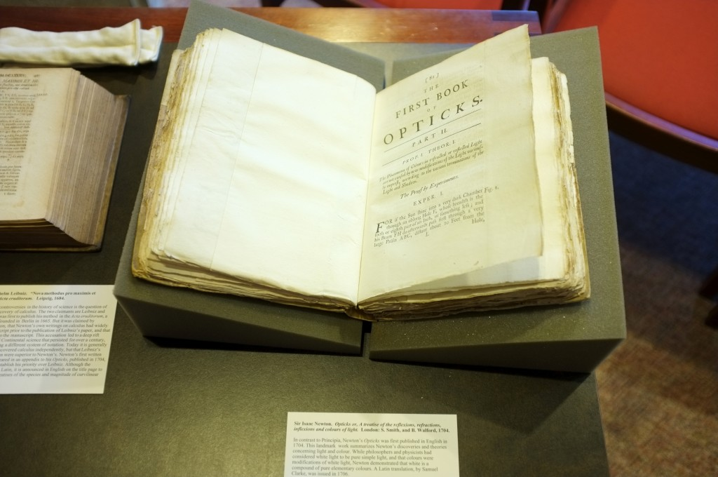 a copy of Isaac Netwon's Opticks from 1704 laying open. the book is very aged looking and has very uneven edges.