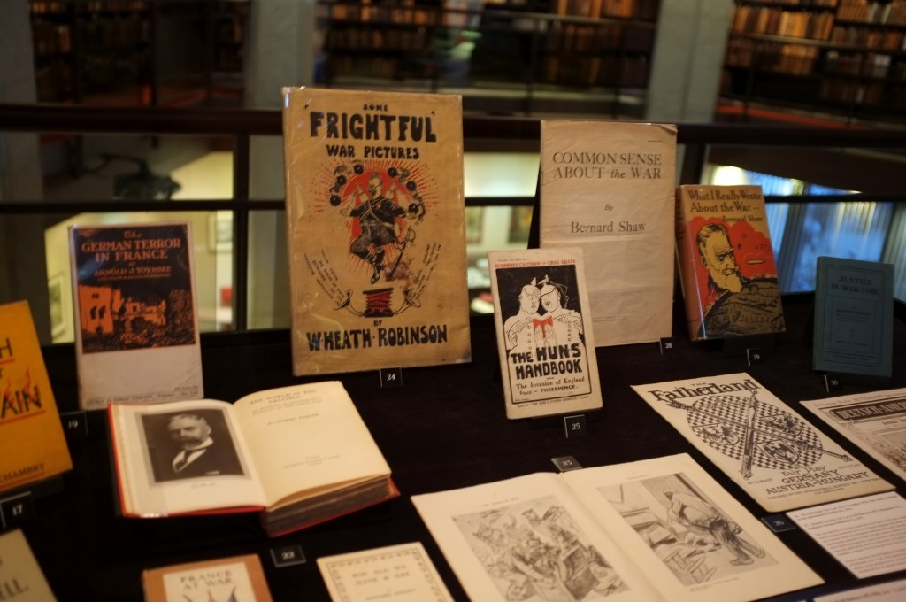 "several open books and front covers of books are shown in a display case. the books are all from the first world war. The ones in focus say ""Frightful war pictures"" another says ""the Huns Handbook"""