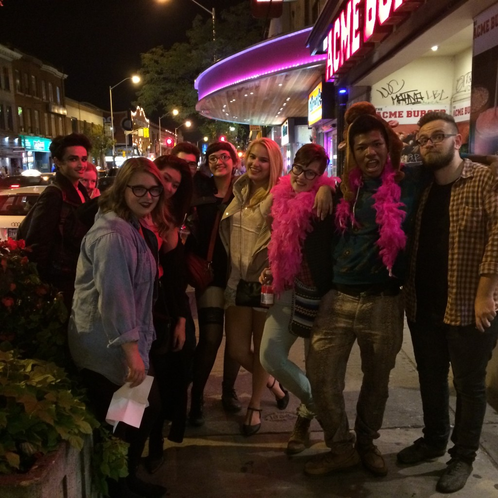 Me posing with my group of friends outside the Bloor Cinema. We're all smiling and making weird faces. I am once again wearing a cow hat, and have a pink boa on me for some reason.