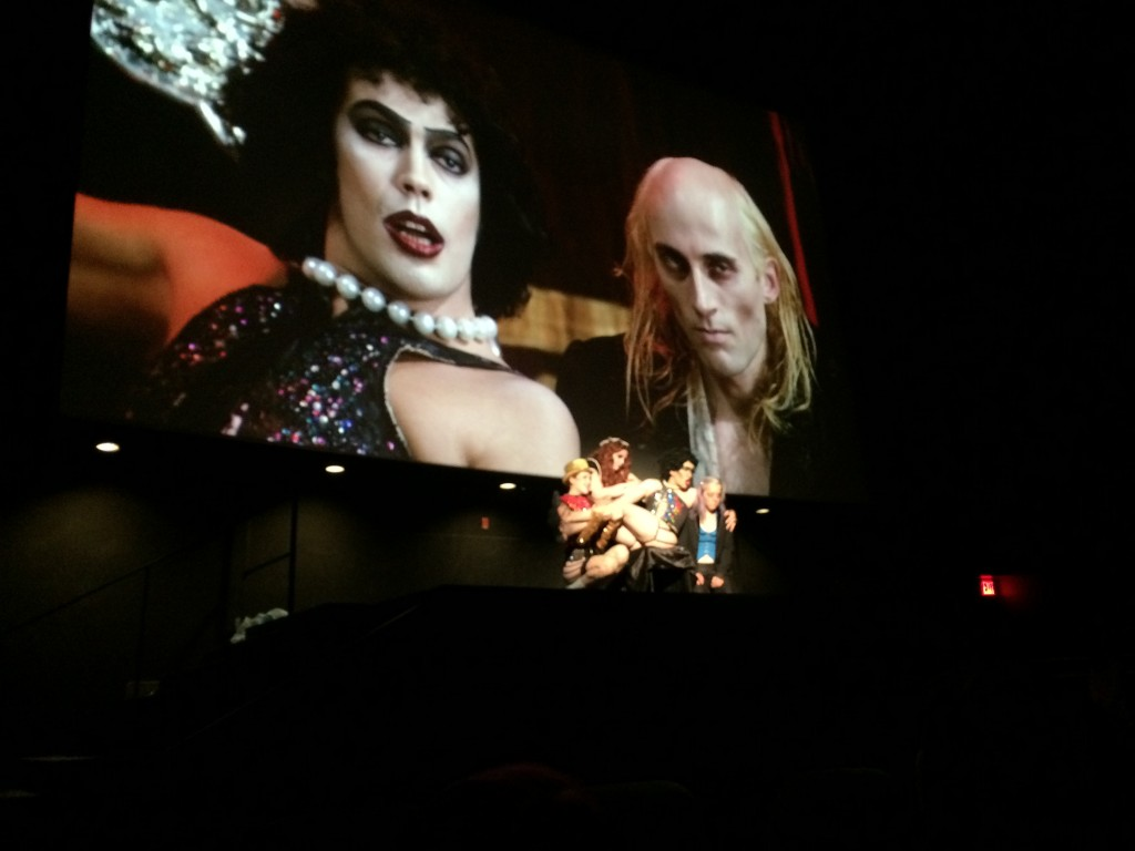 "The Rocky Horror Picture film is playing in the background. The ""Sweet Transvestite"" scene. The Shadow Cast is in front of the screen. Dr. Frank-N-Furter is sassily sitting on a lounge chair while his minions surround him."