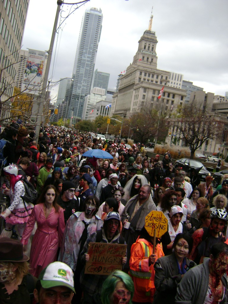 "A photo of a crowd of participants in a ""Zombie Walk"", in which people dress up as zombies and parade about."