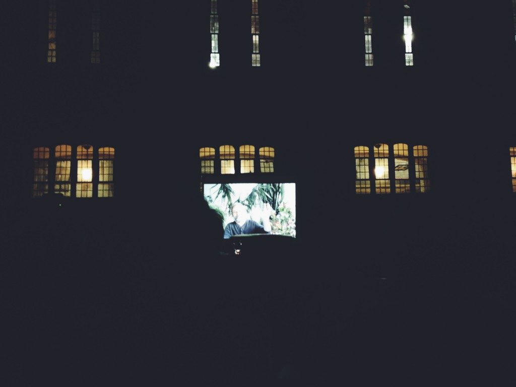 Picture outdoors at night time. There is a screen in the background with a movie playing on it (the details are not visible). Behind the screen where the movie is playing you can see the light shining through old gothic style windows that look into the building'd auditorium.