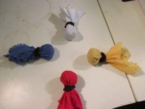 Four small medicine bags, made of yellow, red, blue, and white cloth all pointing outwards in the four directions.