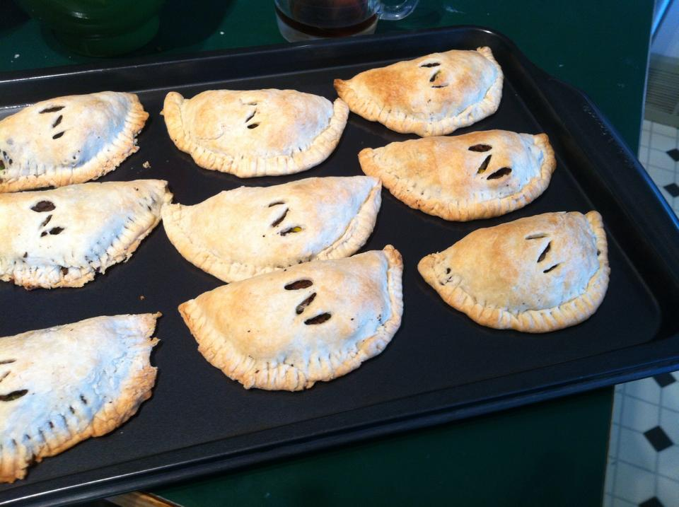 A cookie sheet with nine golden pastry pockets with the letter Z cut into each one