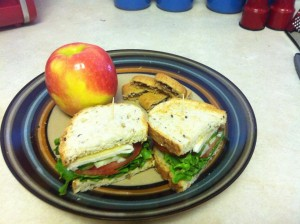 A Pink Lady apple, with two halfs of a turkey and cheese sandwich on Italian bread with all the veggie fixings, plus some chunks of a blueberry granola bar