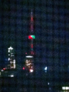 Looking south from my apartment at night, at a Green and Red - lit CN Tower in the holiday season
