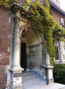 A doorway into Falconer Hall, with aged stone facade with leafy vines draped on the top