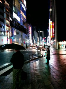 A neon-lit street in Ginza, Tokyo. The ground is shiny with rain. Two people holding umbrellas can be seen standing on the sidewalk.