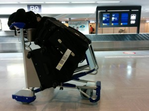 A suitcase on a metal trolley at Narita airport. A conveyor belt for luggage pick-up can be seen in the background.