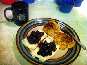 Two golden-brown biscuits next to two two crepe-like creations topped with fresh blueberries